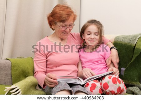 happy grandmother and granddaughter read book together, they sit on couch next to each other and grandma embrace girl - stock photo