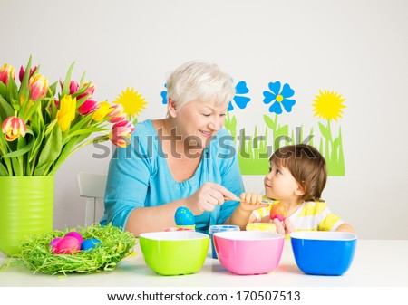 Happy grandmother and grandson color eggs for Easter at home - stock photo