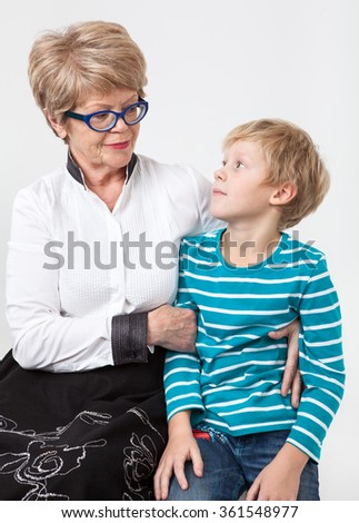 Happy grandmother and grandson sitting together and looking each other, portrait on a gray background - stock photo