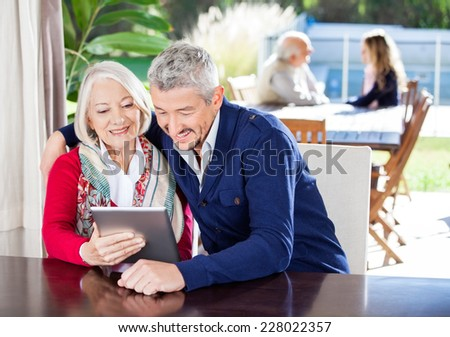 Happy grandmother and grandson using digital tablet with family in background at nursing home - stock photo