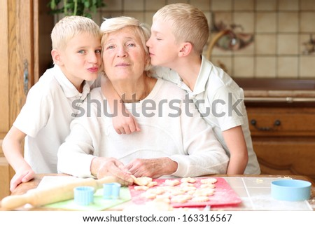 Happy grandmother enjoying time together with loving caring grandchildren, two teenager boys, baking delicious cookies - stock photo