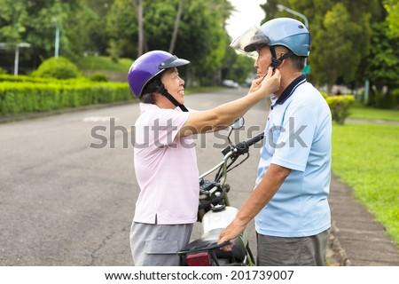 happy grandmother help grandfather to wear a helmet - stock photo