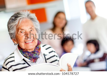 Happy grandmother holding a book of recipes and smiling - stock photo