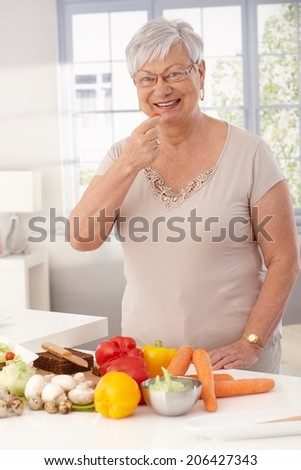 Happy grandmother standing in kitchen using fresh raw materials to prepare healthy food. - stock photo