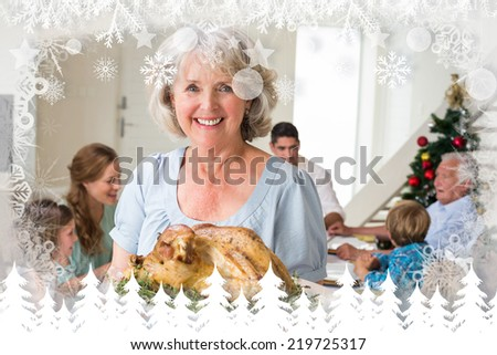 Happy grandmother with Christmas meal against fir tree forest and snowflakes - stock photo