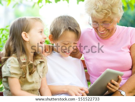 happy grandmother with grandchildren using tablet PC, outdoors - stock photo