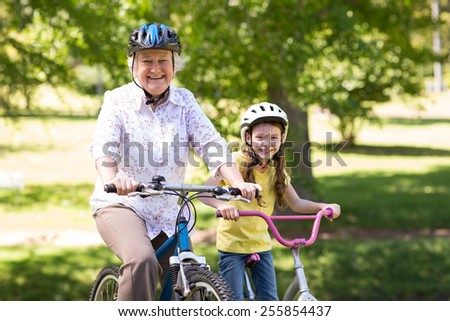 Happy grandmother with her granddaughter on their bike on a sunny day - stock photo
