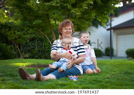 Happy grandmother with two little boys celebrating July 4th - stock photo