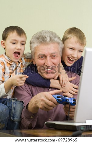 happy grandparent with their grandchildren play on the computer - stock photo