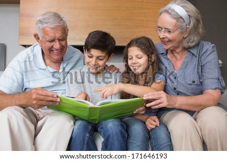 Happy grandparents and grandkids looking at album photo in the living room - stock photo