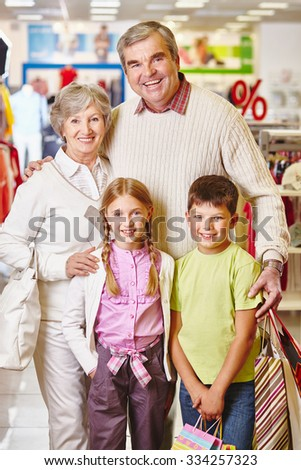 Happy grandparents and their grandchildren with paperbags visiting sale in the mall before Christmas - stock photo