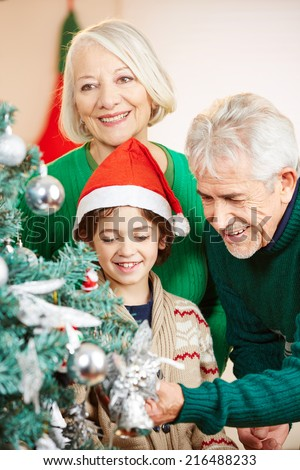 Happy grandparents decorating the christmas tree with their grandson - stock photo
