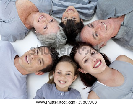 Happy grandparents, parents and children lying on floor with heads together - stock photo