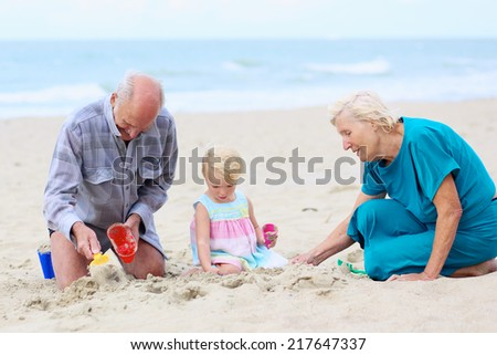 Happy grandparents playing with their granddaughter, cute toddler girl, at the beach building sand castles with plastic toys - active retirement concept - stock photo