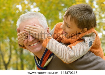 happy grandson with his grandfather on a walk in the park in autumn - stock photo
