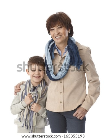 Happy granny hugging little grandson, both smiling and looking at camera. - stock photo