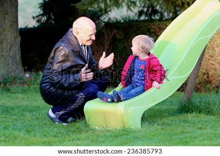 Happy great grandfather with his adorable granddaughter, cute toddler girl, playing on the slide in the garden at backyard of the house on a sunny day - stock photo