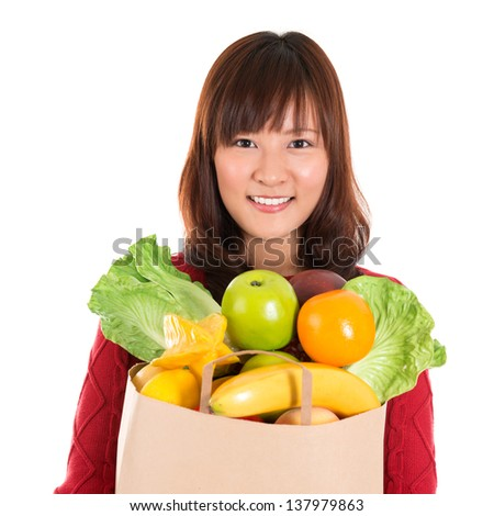 Happy grocery shopper. Smiling young Asian woman holding paper shopping bag full of groceries isolated on white. - stock photo