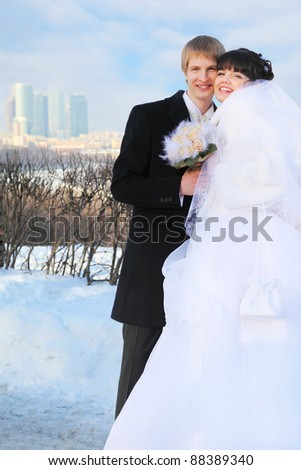 happy groom and bride holding bouquet of roses and look at camera at winter outdoors - stock photo