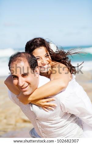 happy groom and bride piggyback on beach - stock photo