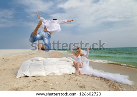 Happy Groom flying on bed to his bride on the beach - stock photo