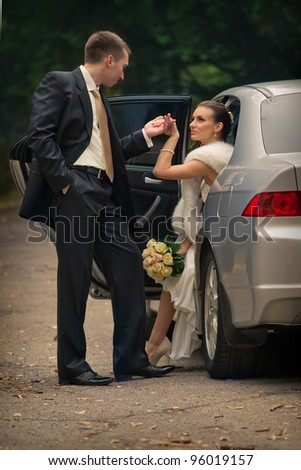Happy groom helping his bride out of the wedding car. - stock photo