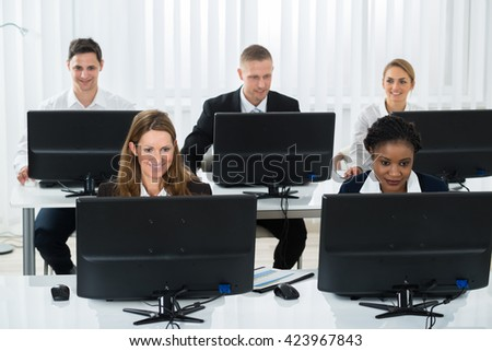 Happy Group Of Businesspeople Working On Computers In Office - stock photo