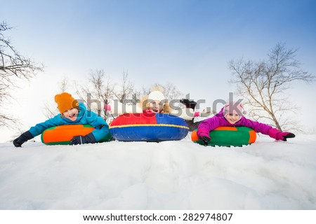 Happy group of children slide on tubes in a row - stock photo