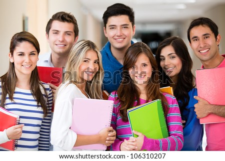 Happy group of college students smiling and holding notebooks - stock photo