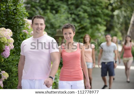 happy group of couples on a walk outdoors - stock photo