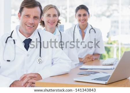 Happy group of doctors posing at their desk with a laptop computer - stock photo