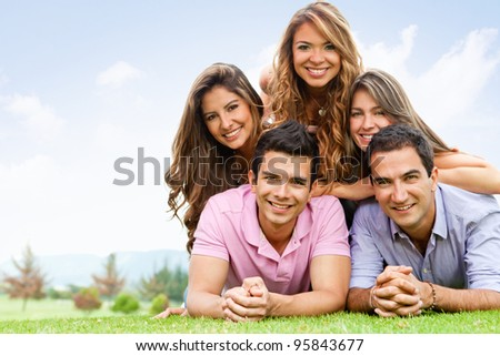 Happy group of friends hanging out outdoors - stock photo