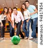 Happy group of friends having fun bowling - stock photo