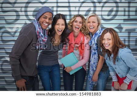 Happy group of friends laughing together on graffiti background - stock photo