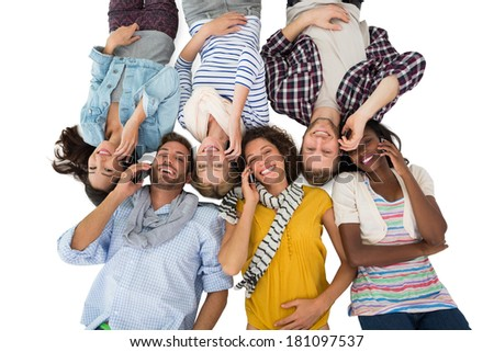 Happy group of friends lying on the floor on their phones on white background - stock photo