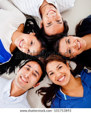 Happy group of friends lying on the floor together - stock photo