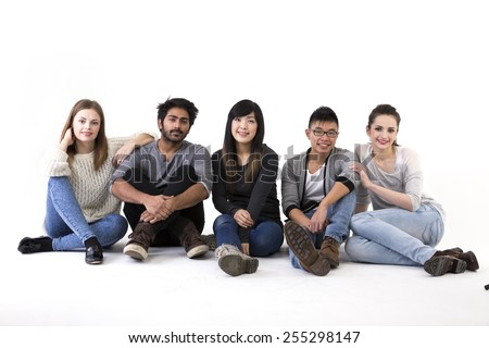 Happy group of friends sitting on floor. Mixed race group. Isolated on a white background. - stock photo