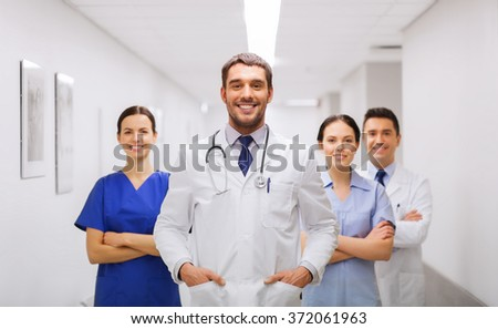 happy group of medics or doctors at hospital - stock photo