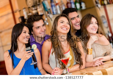 Happy group of people at the bar having a drink - stock photo