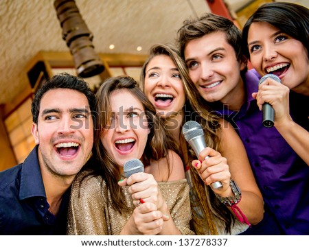 Happy group of people karaoke singing at the bar - stock photo