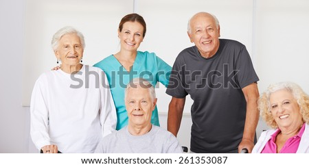 Happy group of senior citizens in nursing home with geriatric nurse - stock photo