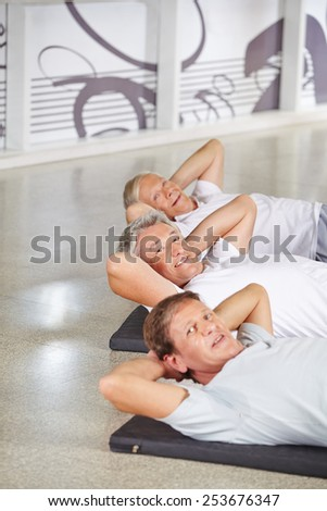 Happy group of senior people doing crunches in a gym - stock photo