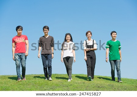 Happy group of students walking and talking at the park - stock photo