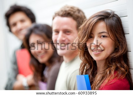 Happy group of students with notebooks against a wall - stock photo