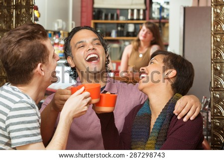 Happy group of three diverse adults laughing with coffee cups - stock photo