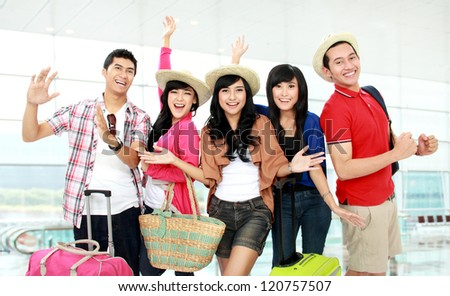Happy group of tourists looking to camera and smile - stock photo