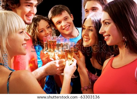 Happy group of young friends touching the glasses with each other - stock photo