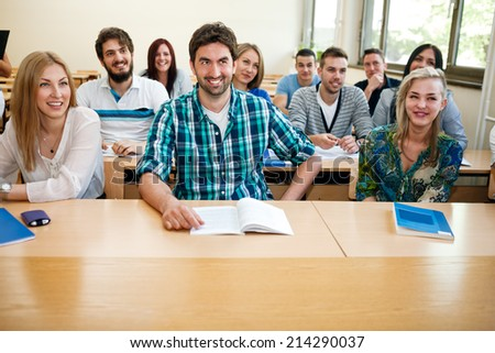 Happy group of young students in a classroom - stock photo