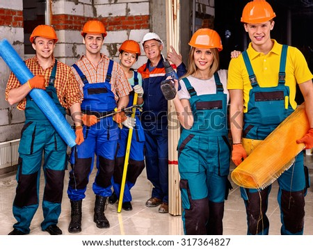 Happy group people in builder uniform. - stock photo