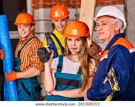 Happy group people in builder uniform looking at camera. - stock photo
